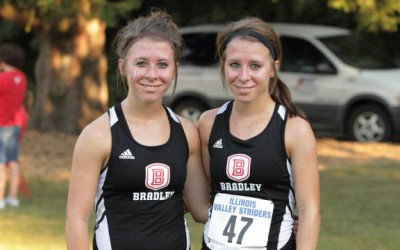 Caitlin and Kristen Busch pose together after a cross country race. Photo via bradleybraves.com.