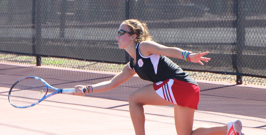 Sophomore Aimee Manfredo reaches for a return during a match. Photo by Ann Schnabel.