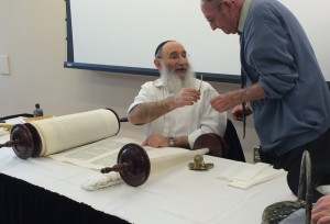 Expert Scribe Rabbi Yochanan Nathan pens the final letters of the Bradley University Torah scroll Sun- day in Westlake Hall. Photo by Maddie Gehling.