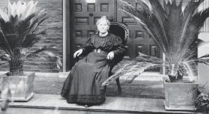 Lydia reclines in a chair on the stoop of her home on Moss Avenue. photo by Special Collections. Bradley University Library
