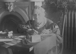Lydia works on business documents at a table in her home. photo by Special Collections. Bradley University Library