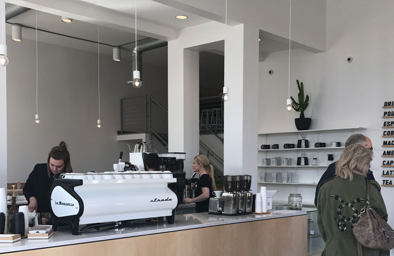 An employee at Zion Coffee Bar works behind the counter at the new shop, which opened Feb. 3 at 803 SW Adams St. in the Peoria Warehouse District. photo by Tori Moses
