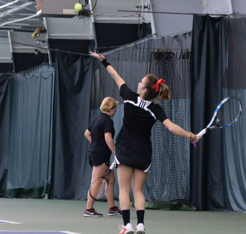 Junior Aimee Manfredo lifts the ball in the air in preparation for a serve in a match earlier this winter. photo by Justin Limoges